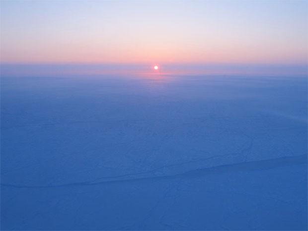 Sol nasce sobre a cobertura de gelo próxima ao Polo Norte (Foto: James Yungel/Nasa/Divulgação)