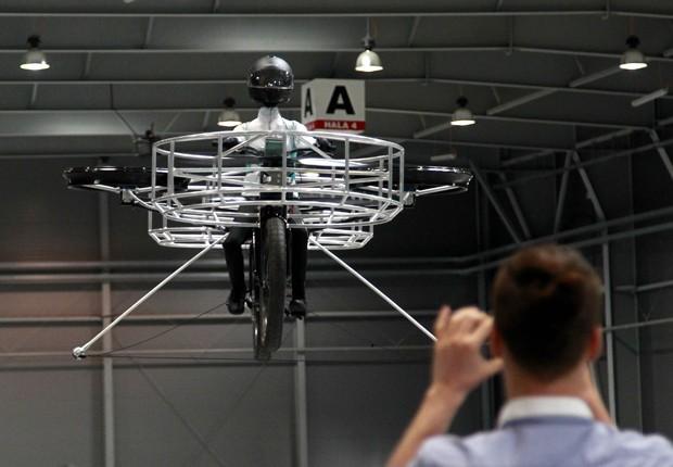 Designers tchecos apresentam uma bicicleta voadora em uma feira em Praga, nesta quarta-feira (12). O objeto é mantido no ar por seis propulsores movidos à eletricidade (Foto: Petr Josek/Reuters)