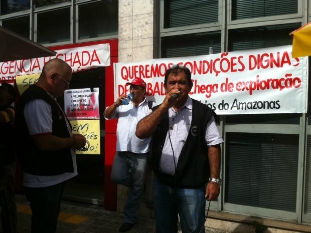 Manifestante protesta em frente a agência bancária no Centro de Manaus (Foto: Girlene Medeiros /G1 AM)