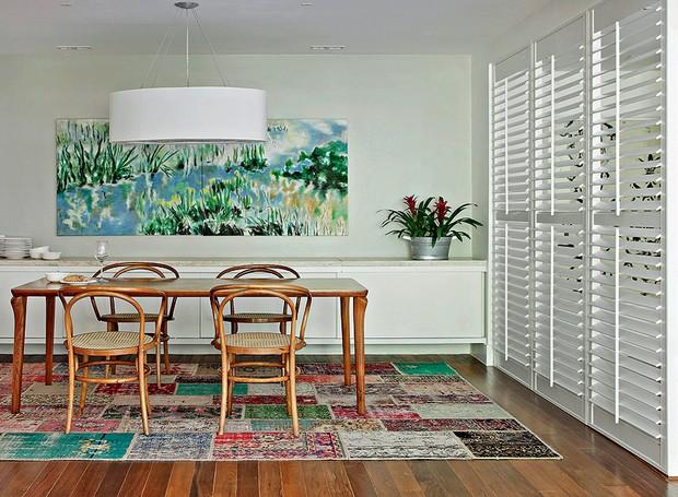 Como a sala de jantar ficava logo na entrada da casa da apresentadora Patricya Travassos, a designer de interiores Paola Ribeiro instalou uma brise para criar o corredor. O ambiente ficou colorido e calmo com o quadro e o tapete de patchwork (Foto: Denilson Machado/MCA Estúdio)