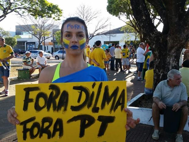 Com o rosto pintado, jovem segura cartaz de 'Fora Dilma, Fora PT' em Sorriso (Foto: Rachel Rocha/ Centro América FM)