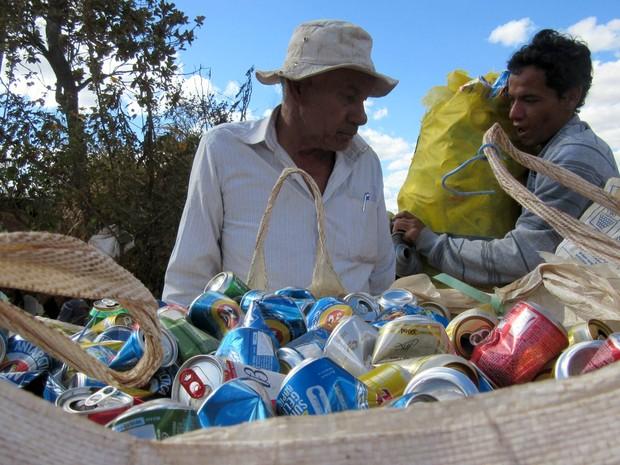 O catador Santiago Sousa carrega um dos sacos de 30 kg de latinhas para a pesagem da cooperativa (Foto: Alexandre Bastos/G1)
