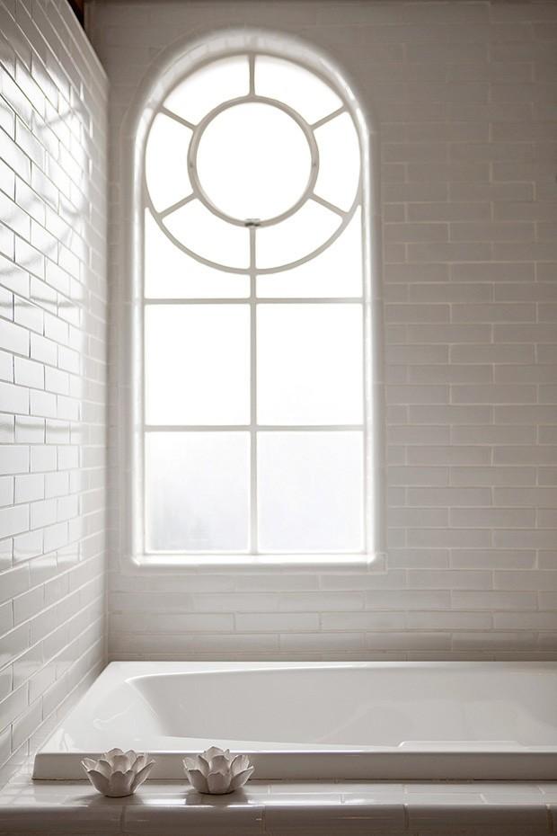 A janela de desenho mais clássico, inerente ao estilo do prédio, integra-se ao visual do banheiro, que tem paredes revestidas de cerâmica branca: simples e chique (Foto: Marco Antonio / Casa & Jardim)