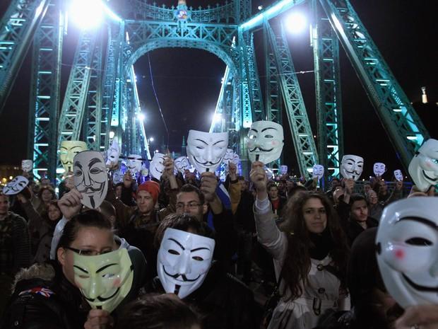 Manifestantes seguram suas máscaras de Guy Fawkes na Ponte da Liberdade, durante uma manifestação de apoiantes do movimento Anonymous, em Budapeste, na Hungria (Foto:  Bernadett Szabo/Reuters)
