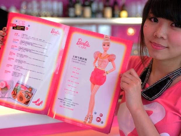 Garçonete mostra o menu durante a cerimônia de abertura de um restaurante temático Barbie (Foto: AFP PHOTO / Sam Yeh)