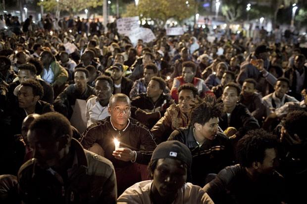 Munidos de velas e cartazes, imigrantes africanos em Israel foram às ruas da capital Tel Aviv, neste sábado (28), para protestar contra ações do governo que os têm confinado em centros penitenciários. (Foto: Nir Elias/France Presse)
