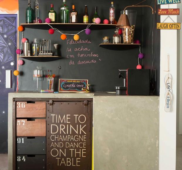 Logo na entrada deste apartamento, os convidados da moradora podem aproveitar para tomar um drinque. As bebidas e os acessórios do pequeno bar foram organizados em prateleiras. O móvel em L foi desenhado pela arquiteta do projeto, Sara Oleiro (Foto: Edu Castello/Editora Globo)