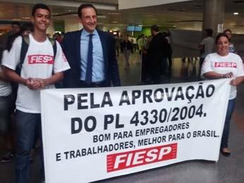 O presidente da Fiesp, Paulo Skaf, ao lado de faixa em apoio ao PL 4.330 (Foto: Isabella Calzolari/G1)