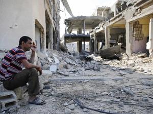 3/8 - Palestino fuma sentado em meio às ruínas de edifícios destruídos após bombardeios no sul de Gaza (Foto: Finbarr O'Reilly/Reuters)