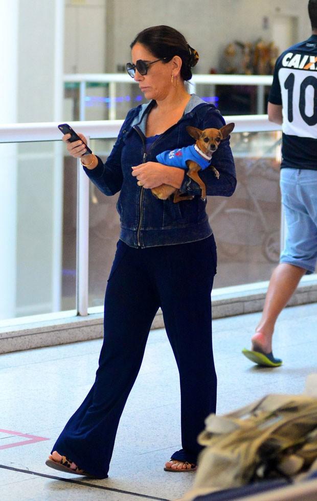 Depois de deixar os filhos no embarque, Glória saiu com celular na mão e um cachorro da raça Pintcher no colo (Foto: Delson Silva/AgNews)