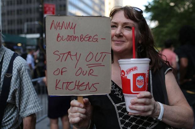 """Manifestante carrega cartaz em que se lê: """"Babá Bloomberg, fique longe da minha cozinha"""" (Foto: Spencer Platt / Getty Images / AFP)"""