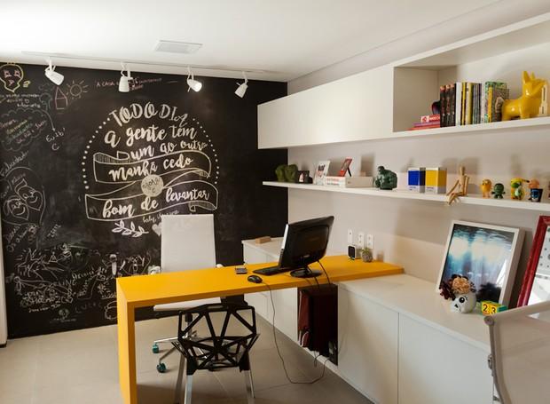 Escritório | O ambiente mais divertido do lar é o escritório. A mesa de nanoglass amarela da Carioca Granitos dá um toque especial ao cômodo, junto com a parede de lousa. Prateleiras planejadas pela Stanza Móveis (Foto: Maurício Pokemon/Divulgação )