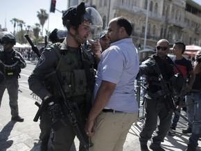 Policial israelense discute com palestino que protestava contra marcha  (Foto: Ahmad Gharabli/AFP)