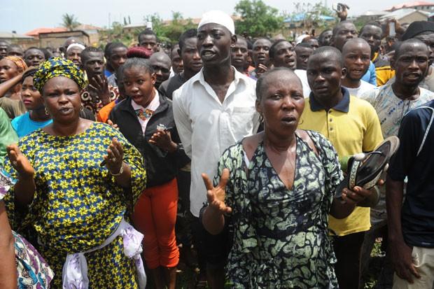 Multidão faz orações por vítimas no local onde corpos em decomposição e ossadas foram encontrados, na Nigéria (Foto: Pius Utomi Ekpei/AFP)