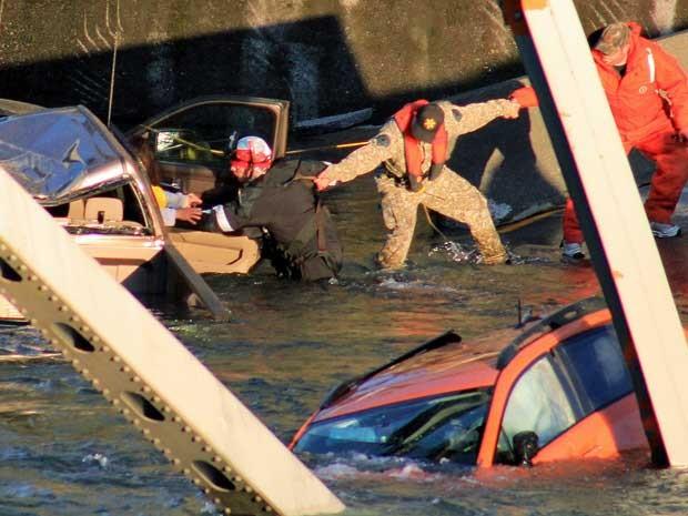 Equipes de resgate formam uma corrente humana para retirar uma mulher que caiu no rio gelado. (Foto: Francisco Rodriguez / AP Photo)