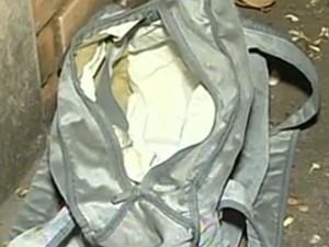 Menino estava dentro de uma bolsa, na frente de uma casa (Foto: Reprodução/TV Anhanguera)