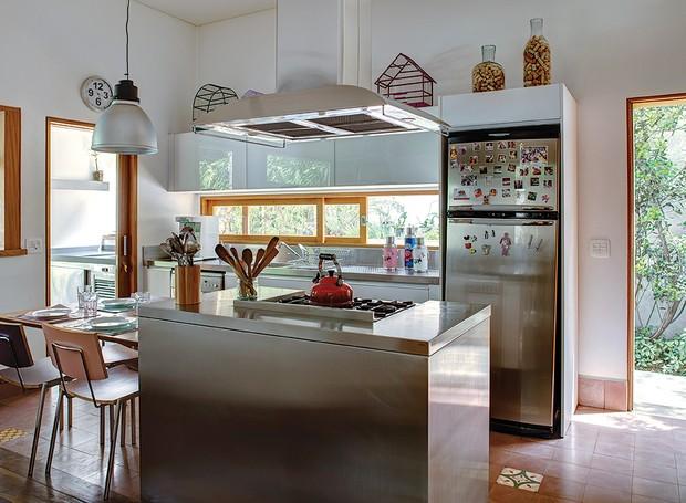 Uma das vantagens de morar em casa é ter uma cozinha assim, integrada com o jardim. Com ilha central e mesa de almoço, o projeto é do arquiteto Jorge Siemsen (Foto: Edu Castello/Casa e Jardim)