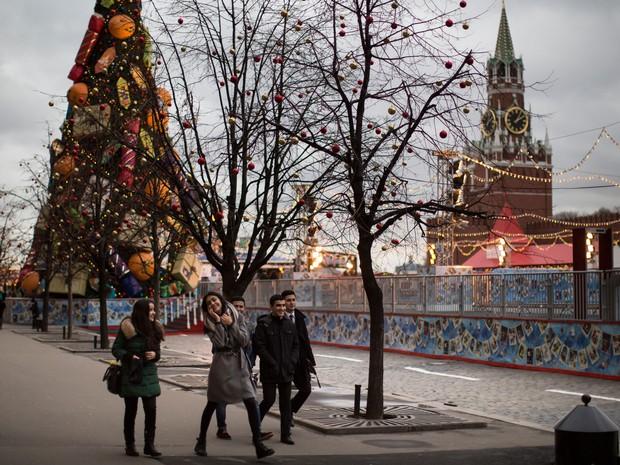 Turistas aproveitam o clima ameno na Praça Vermelha, em Moscou, em foto do dia 23 de dezembro. As temperaturas chegaram a mais de 5º C  no Natal este ano, bem acima do comum para esta época  (Foto: AP Photo/Alexander Zemlianichenko)