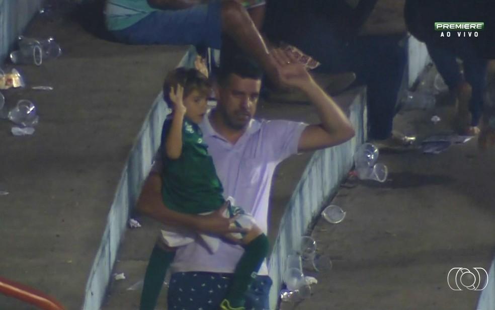 Com filho no colo, torcedor levanta o braço para mostrar que não participa da briga (Foto: Reprodução/ TV Anhanguera)