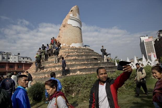 Homem tira selfie em frente a torre Dharahara, em Katmandu, no Nepal, nesta segunda-feira (27)  (Foto: AP Photo/Bernat Armangue)