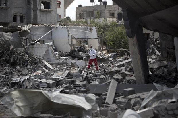 Palestino é visto em meio a destroços de prédios bombardeados em Rafah, na Faixa de Gaza, nesta segunda-feira (4) (Foto: Mahmud Hams/AFP)