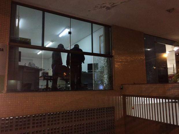 Porta de vidro e parede ficaram danificados pelos tiros (Foto: PM/Divulgação)