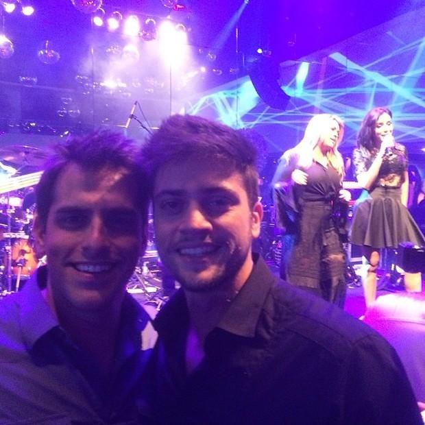 Rodrigo Godoy com um amigo e, ao fundo, Preta Gil canta com Anitta em festa em São Paulo (Foto: Instagram/ Reprodução)