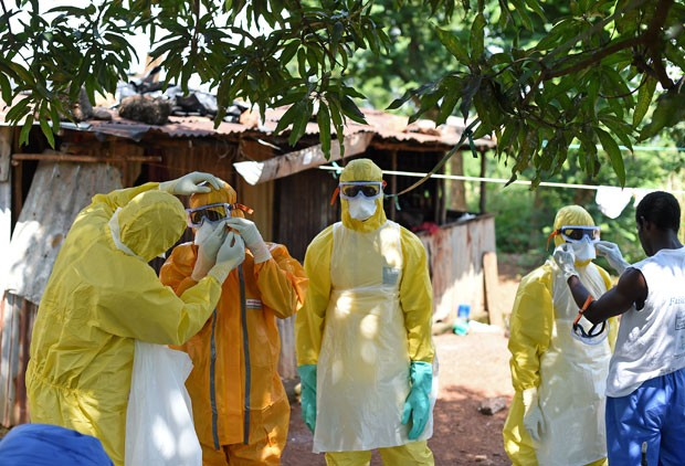 Trabalhadores de saúde da Cruz Vermelha de Serra Leoa se preparam para retirar um corpo de uma vítima de ebola de uma casa em Freetown nesta quarta-feira (12) (Foto: Francisco Leong/AFP)