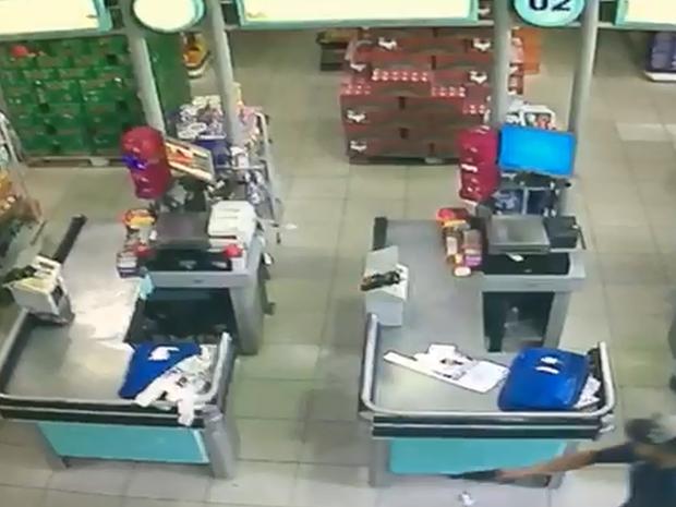 Câmera de segurança registrou momento em que criminoso levanda arma contra funcionários (Foto: Reprodução/Circuito de Segurança)
