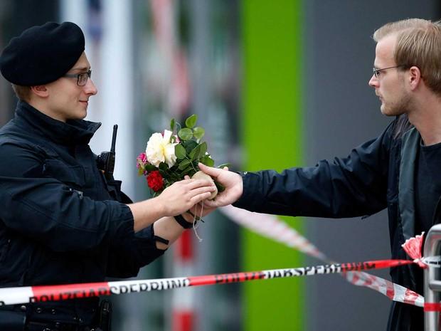 Rapaz oferece flores a um policial para colocá-las em centro comercial (Foto: Michael Dalder / Reuters)