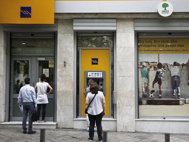 Gregos fazem saques em caixas automáticos ou esperam para entrar em banco nesta sexta-feira (19), em Atenas. Saques aumentaram consideravelmente após o medo de país dar calote em seus credores no fim do mês (Foto: Alkis Konstantinidis/Reuters)