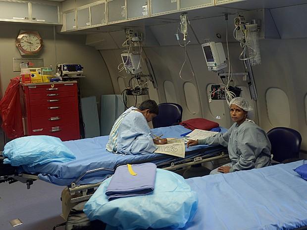 Integrante da equipe médica atende o menino Emanul Sekh, de 8 anos, antes da cirurgia (Foto: Dibyangshu Sarkar/AFP)