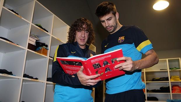 Puyol e Piqué conferem o livro  (Foto: Miguel Ruiz/Site Oficial do Barcelona)