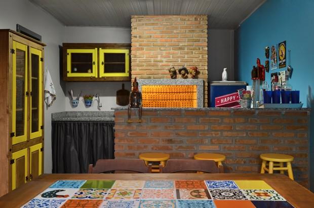 A área externa tem ainda um espaço com churrasqueira para reunir os amigos. A mesa com ladrilhos é um charme! (Foto: Vanessa Bohn/Bohn Fotografias)