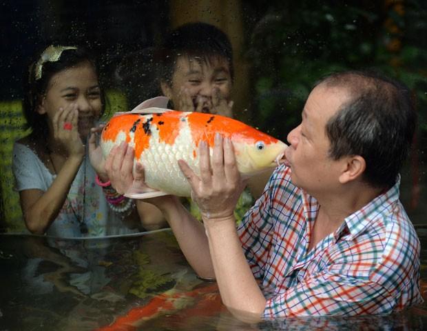 Dono beija carpa em aquário e surpreende crianças em zoo filipino