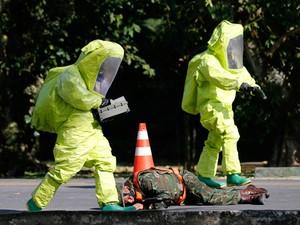 Homens simulam perigo de armas químicas (Foto: Sergio Moraes / Reuters)