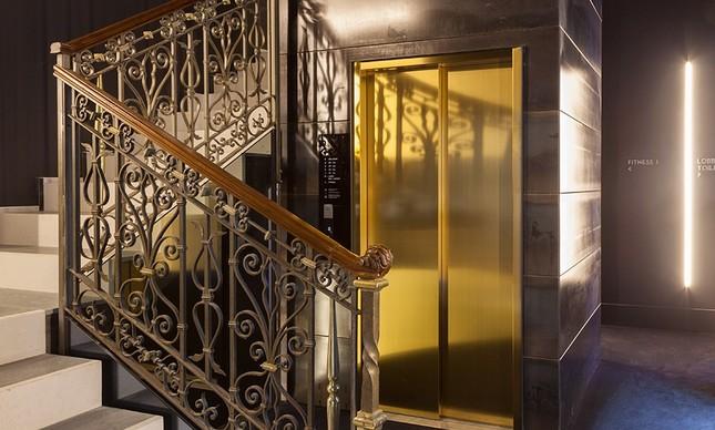 Corrimão em ferro contrasta com a porta dourada do elevador