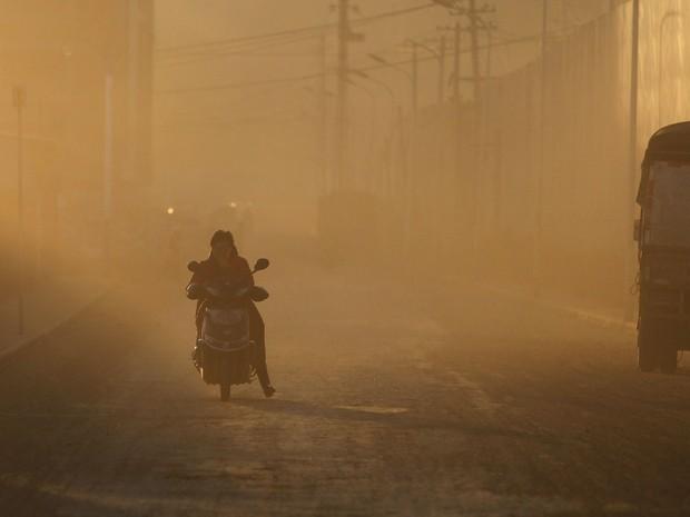 Homem pedala em meio a uma nuvem de poluição em Kunming, na província de Yunnan (Foto: Wong Campion /Reuters)