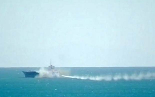 Rastro do míssil é visto no momento em que a réplica de um porta-aviões americano é destruído em exercício militar no Irã (Foto: AP/Iran TV)