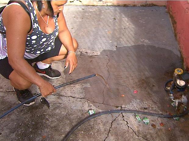 Além da escassez no abastecimento, dona de casa mostra que água vem suja nas torneiras em Batatais, SP (Foto: Carlos Trinca/EPTV)
