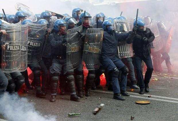 Policiais se protegem de garrafas e pedras atirados pelos manifestantes em Roma (Foto: Alessandro Bianchi/Reuters)