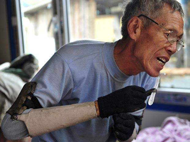 Sun Jifa faz a barba com as próteses caseiras (Foto: Reuters/Sheng Li)