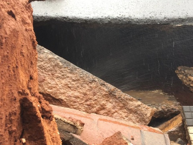 Pelo buraco é possível ver o vazamento e o asfalto oco  (Foto: Evandro Cini/ TV TEM)