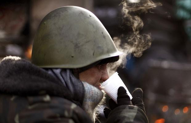 Manifestante antigoverno bebe chá em barricada de Kiev, neste sábado (1º) (Foto: Vasily Fedosenko/Reuters)