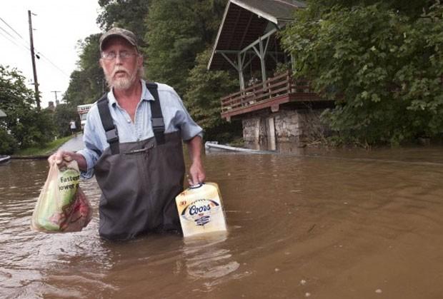 Em setembro de 2011, o americano Mike Ingolls foi flagrado enfrentando uma rua inundada enquato levava para sua casa em Hellam Township, no estado da Pensilvânia (EUA), uma caixa de cerveja (Foto: AP)