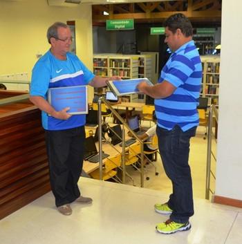 Orcy Nogueira entrega álbum ao coordenador da biblioteca (Foto: Adelcimar Carvalho)