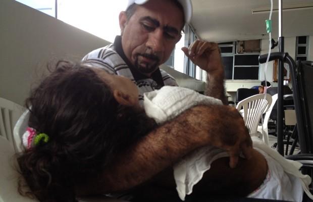 Após a sessão, pai segura a menina: 'Ela está ficando 100%' (Foto: Fernanda Borges/G1)