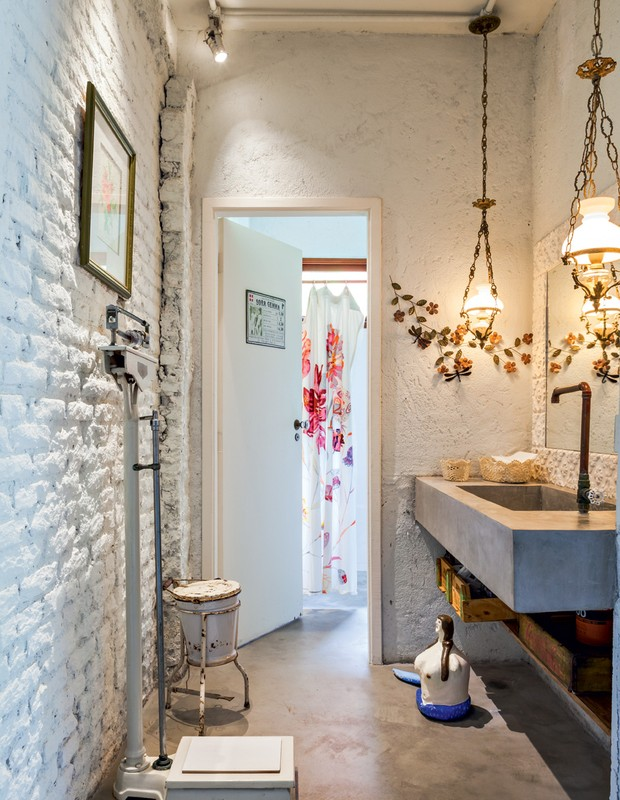 A delicadeza das luminárias antigas no lavabo contrastam com a torneira de cobre rústica, os canos aparentes e a pia de concreto. Adorei a balança herdada da casa de sua avó na Bahia. (Foto: Lufe Gomes/Life by Lufe)