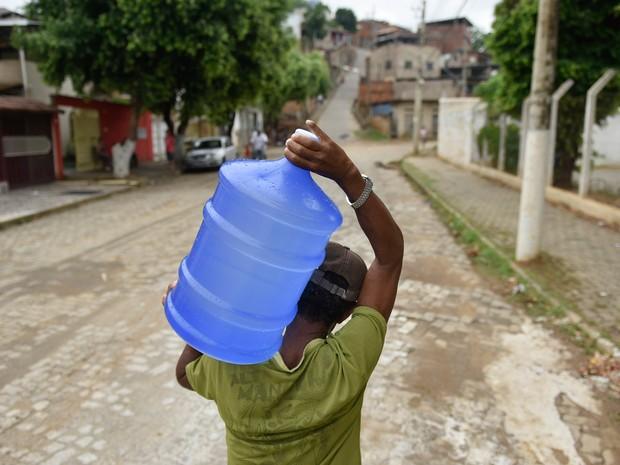 Um homem carrega um galão de água no bairro de São Raimundo, em Governador Valadares (MG). A cidade enfrenta problemas de abastecimento após o rompimento de duas barragens de rejeitos da mineradora Samarco ter contaminado o Rio Doce (Foto: Douglas Magno/O Tempo/Estadão COnteúdo)
