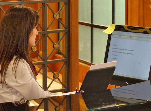 A secretária digita um bilhete secreto para Manoela (Foto: Guerra dos Sexos/ TV Globo)